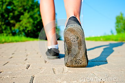 Female legs in sneakers close up running down the road
