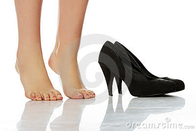 Female legs standing on toes next to high heels
