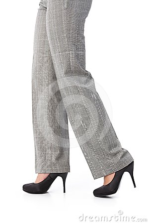 Female legs in trousers and high heels