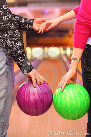 Female and male hands with balls in bowling club