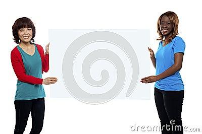 Female marketing executives holding billboard