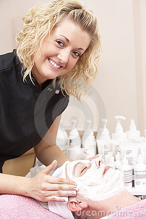 Female masseuse giving client facial