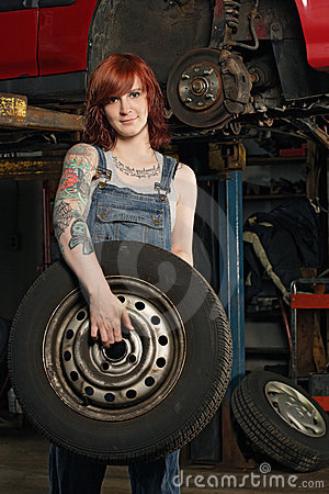 Female mechanic changing tires