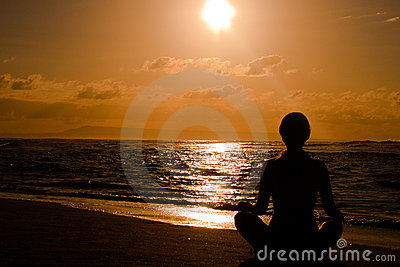 Female meditating on the beach