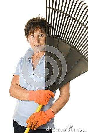Female middle age senior gardener leaf rake
