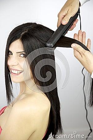 Female model getting long hair ironed