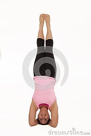 female model in sirsasana yoga pose balancing vert stock