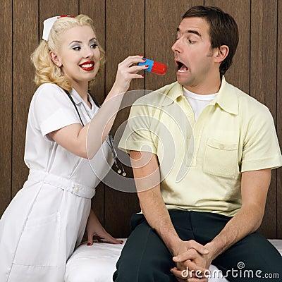 Female nurse giving man giant pill.