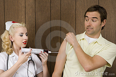 Female nurse giving man shot with giant syringe.