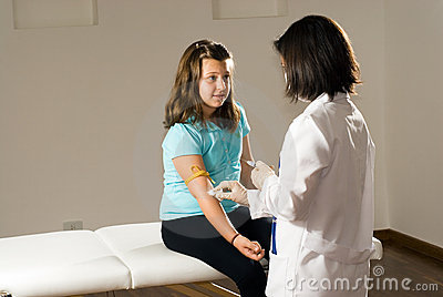 Female Nurse Preparing a Girls Arm for Vaccination