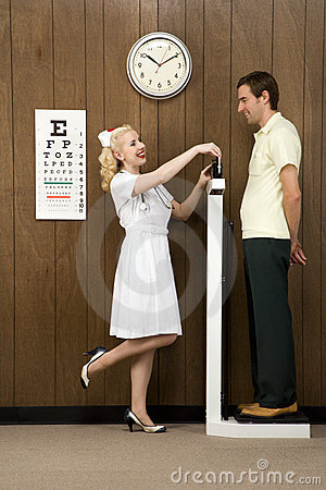 Female nurse weighing man on scale.