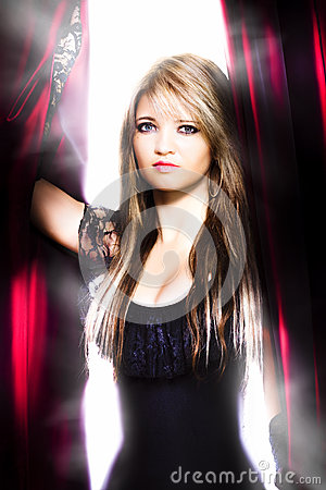 Female performer behind the stage curtain light