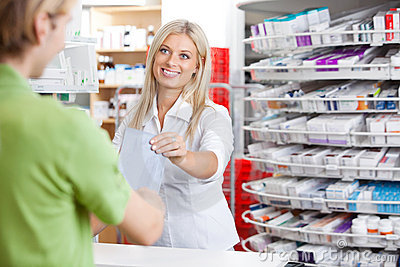 Female Pharmacist With Customer at Counter