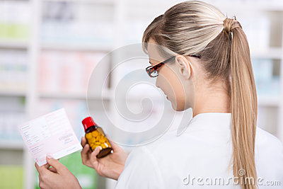 Female pharmacist holds prescription and medicine
