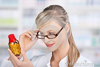 Female pharmacist reading the medicine label