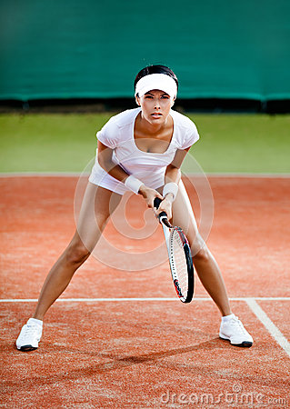 Female player competes at the clay tennis court