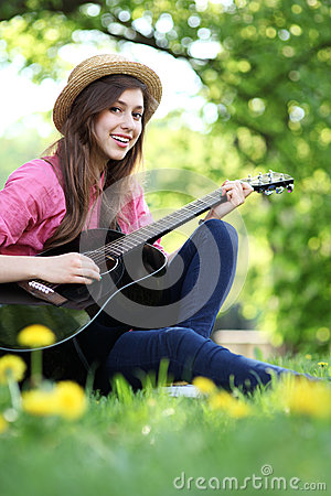 Female playing guitar in park