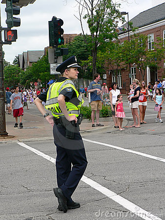 Female police officer watches Fourth of July parad Editorial Stock Image