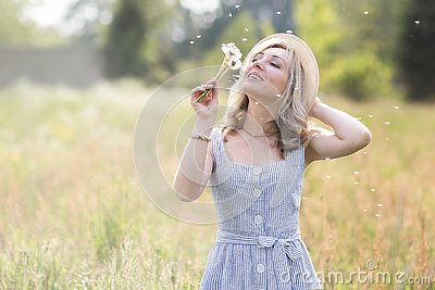 Female portrait outdoors. a woman in a straw hat in a flower field with a bouquet of wild flowers. Stock Photo