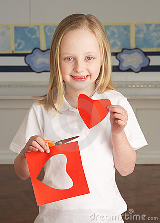 Female Primary School Pupil Cutting Out Shapes