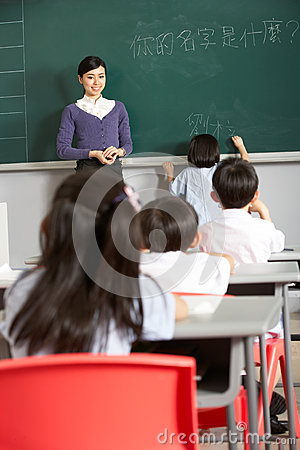 Female Pupil Writing On Blackboard In School