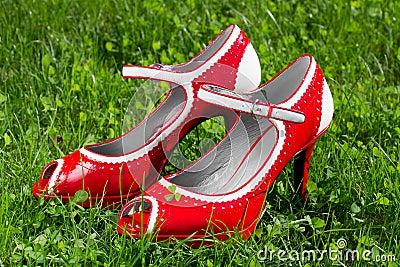 Female red high heel shoe on green grass