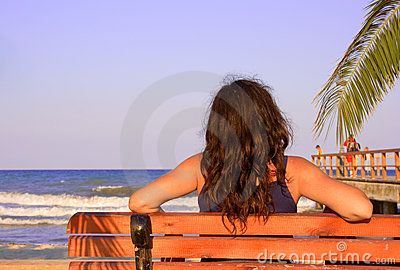 Female relaxing on a beach bench