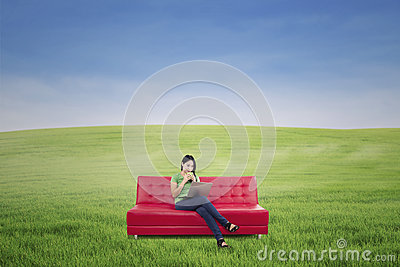Female relaxing on red sofa outdoor