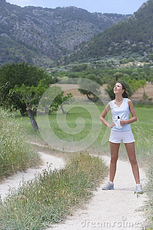 Free Female Runner Standing With Water Bottle On Rural Path Royalty Free Stock Photo - 41717045