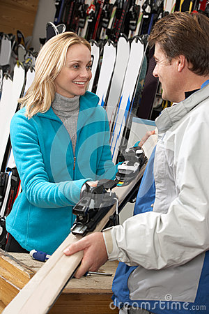 Female Sales Assistant Handing Skis To Customer