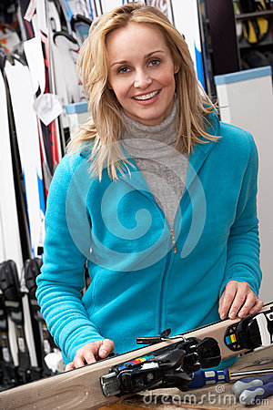 Female Sales Assistant With Skis In Hire Shop