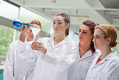 Female science students pouring liquid in a flask