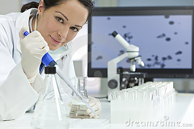 Female Scientist With Pipette In Laboratory