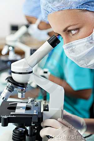 Female Scientists Using Microscopes in Laboratory