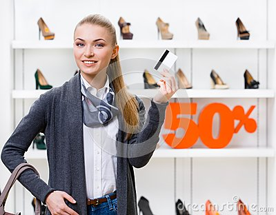 Female showing credit card in footwear shop