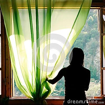 Female silhouette at open window