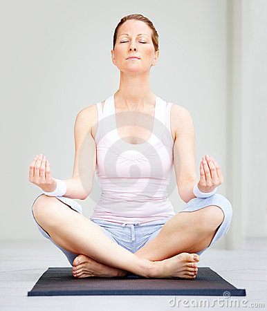 Female sitting on yoga mat meditating