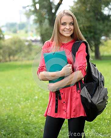 Female smiling student outdoors holding a notebook