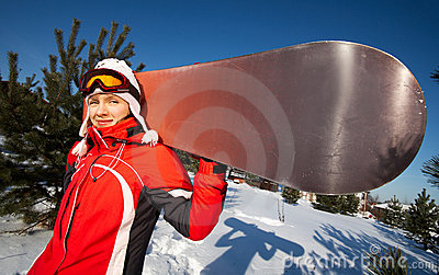 Female snowboarder over blue sky in forest