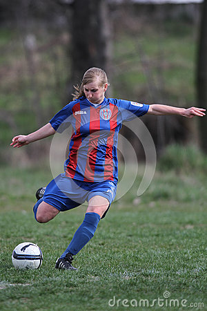 Female soccer player kicking the ball