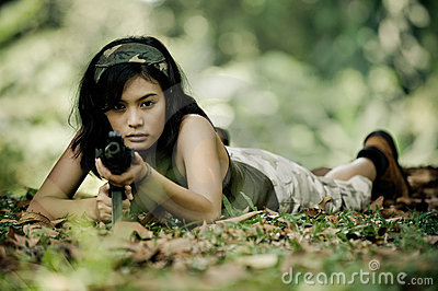 Female soldier aiming machine gun