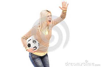 A female sport fan holding a football and shouting