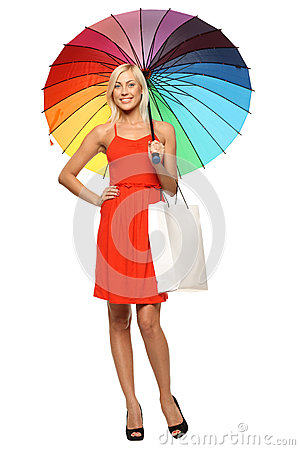 Female standing under umbrella with shopping bag