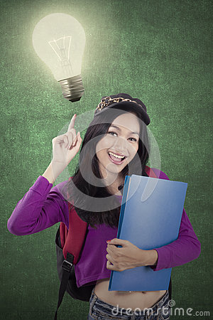 Free Female Student Pointing At A Bright Bulb Royalty Free Stock Image - 98707116