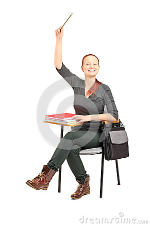 Female student sitting on a chair and raising her hand