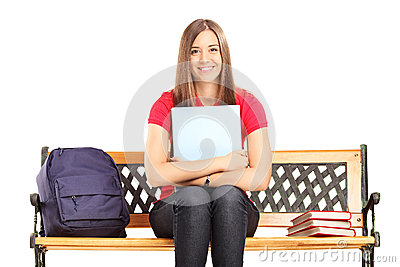 Female student sitting on a wooden bench and holding a notebook
