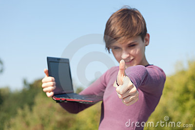 Female student with thumb up using laptop