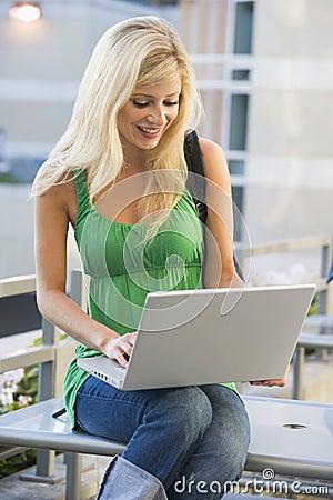 Female student using laptop outside
