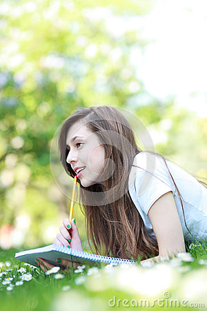 Female student with workbook outdoors