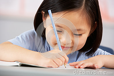 Female Student Working At Desk In School